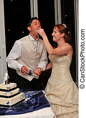 Bride feeding the groom wedding cake with her hand and smiling at him
