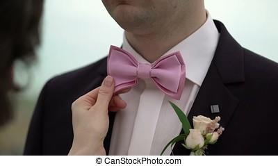 Bride fixing grooms bow tie shot