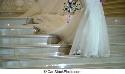 Bride goes downstairs at the ladder in palace