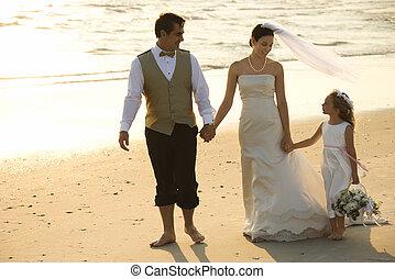 Bride, groom and flower girl. - Caucasian mid-adult bride,...