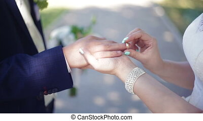 Bride groom puts the ring on her finger at a wedding...