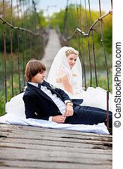 bride groom sitting on the bridge