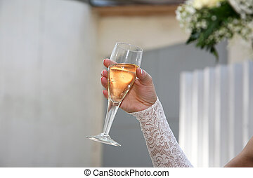 bride hand holds a glass with a drink