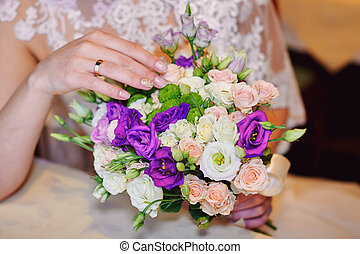 Bride hand with gold ring a wedding bouquet on table
