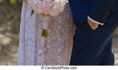 Bride hold bouquet of pink peones