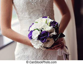 bride holding a bouquet in the hands of the purple flowers