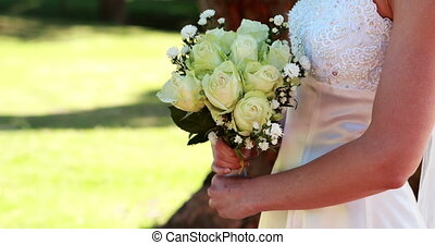 Bride holding a bouquet in the park