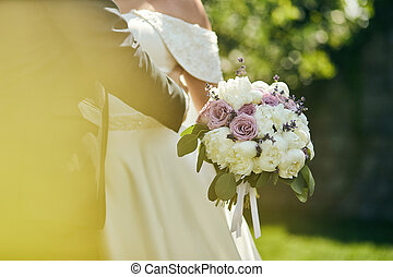 Bride holding a wedding bouquet in the hands standing near groom
