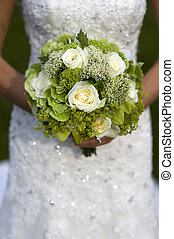 bride holding a wedding bouquet of white roses