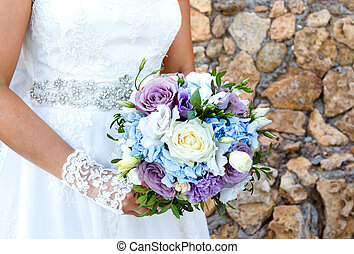 Bride holding beautiful bouquet of roses outdoors.