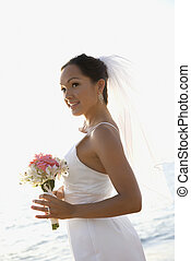 Bride holding bouquet on beach.