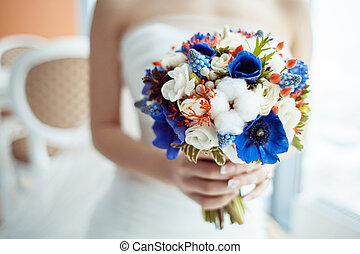 Bride holding bouquet - A bride in a strapless dress holding...