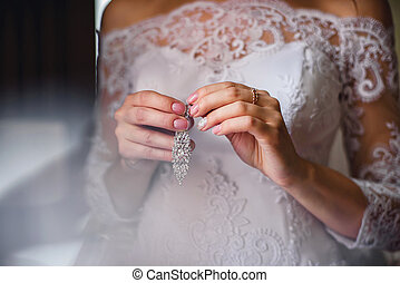bride holding Bridal silver earrings in her hands on white dress background with French manicure