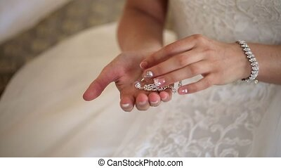 Bride holding earrings