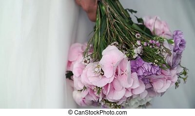 Bride holding flowers bouquet with violet flowers veil...
