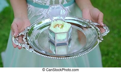 Bride holding plate with wedding rings