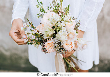Bride holding the wedding bouquet, with beautiful flowers rustic style