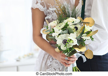 Bride holding wedding bouquet. Close up
