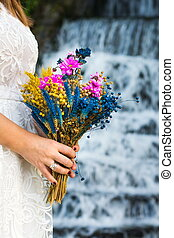 Bride holding wedding bouquet in front of a waterfall