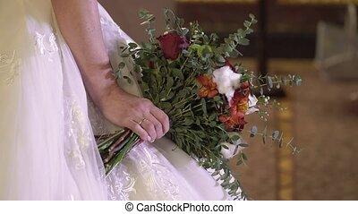 Bride holding wedding bouquet indoors