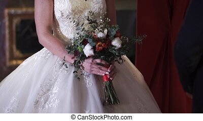 Bride holding wedding bouquet indoors