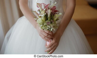 Bride holding wedding bouquet of white and pink calla near...