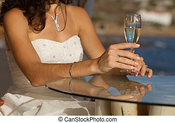 Bride holding wedding glass with wine