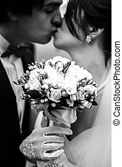 Bride holds a bouquet  in hands in white gloves while groom kisses her
