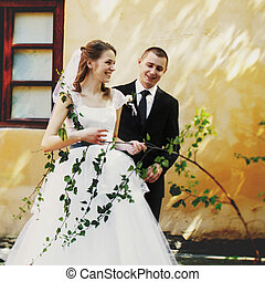 Bride holds a delicate brench while posing with a groom
