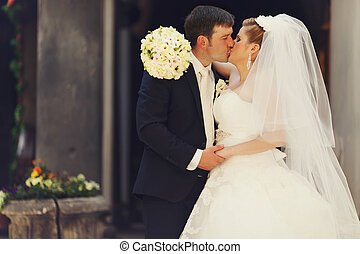Bride holds a hand with bouquet on groom's shoulders while kissing