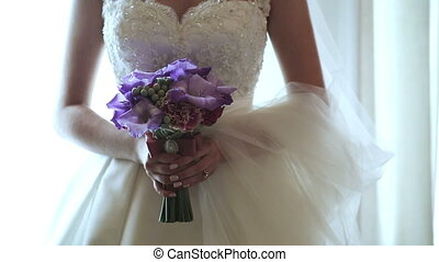 Bride holds a wedding bouquet in her hands at home