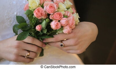 Bride holds a wedding bouquet in her hands shot in slow motion  close up