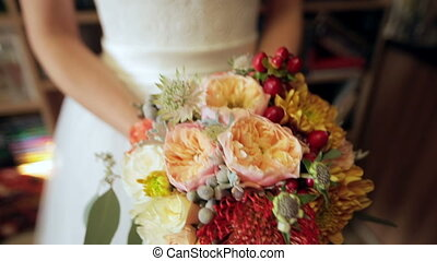 Bride holds a wedding bouquet in her hands