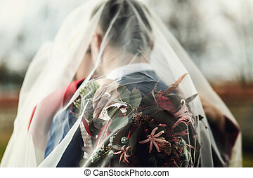 Bride holds a wedding bouquet on groom's back while they hug under a veil