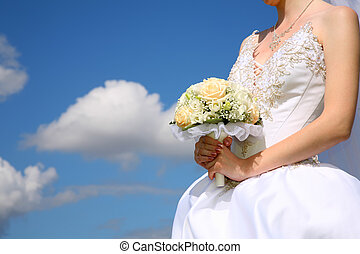 bride holds bouquet against the background of the sky