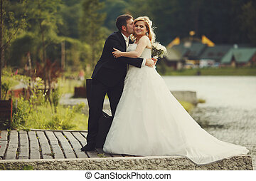 Bride holds groom's hand while he hugs her on the lake's shore