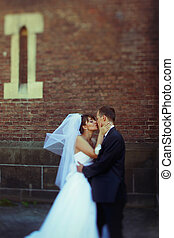Bride holds groom's neck tenderly and kisses him standing behind an old cathedral