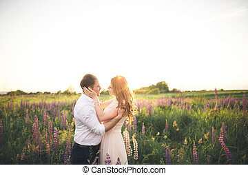 Bride Holds Groomu0027s Neck While He Kisses Her In The Rays Of Sunset