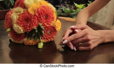 Bride holds hands with wedding bouquet close up