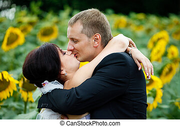 Bride holds her hands on groom's neck while he kisses her behind a field full of sunflowers