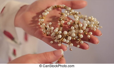 Bride holds in his hands a necklace. Bride holds in hand a...