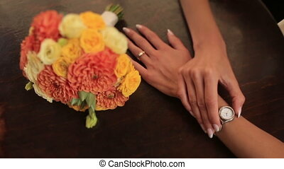 Bride holds watch on her fragile wrist close up.