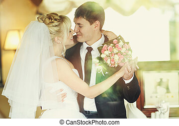 Bride hugs a groom holding a hand with a bouquet around his neck