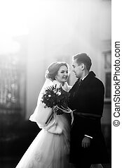 Bride hugs fiance's hand in the light of rising sun