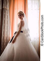 bride in a beautiful dress near the window