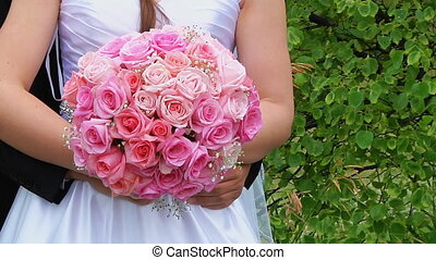 Bride in a designer dress holding a rose bouquet.