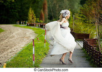 Bride in a dress with violet ribbon whirls on the grey pass