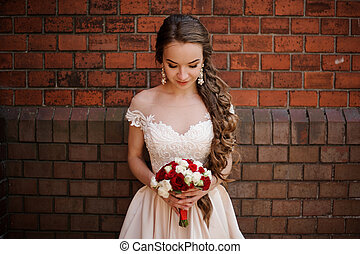 Bride in a wedding dress standing on the background of a red brick wall