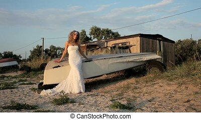 Bride In A Wedding Dress Stands Near The Boat