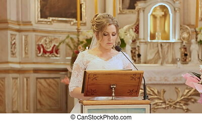 Bride in church at her wedding reading the gospel. God's word.